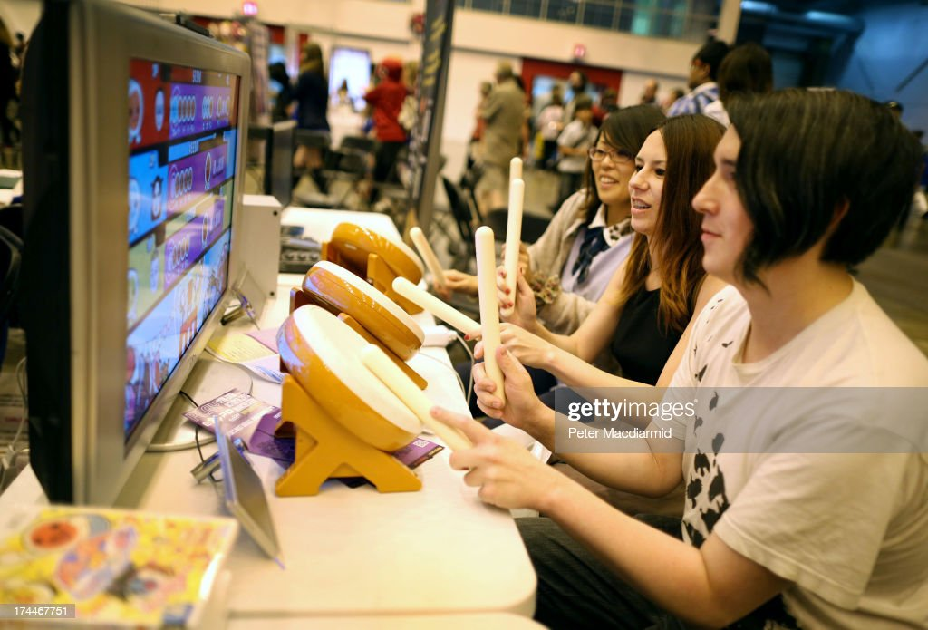 Visitors try out a drumming video game at the Hyper Japan event at Earls Court on July 26, 2013 in London, England. The show is the UK's biggest Japanese Culture event, with stalls selling clothing and artwork. Live music, Japanese food and computer gaming areas are also on show. Many attendees dress up as anime characters or in the lolita fashion widespread in Japan.