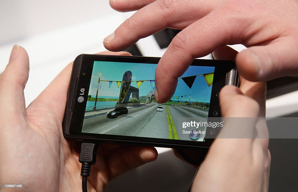 Visitors try out an LG Optimus 3D mobile phone that has a 3D screen at the CeBIT technology trade fair on March 1, 2011 in Hanover, Germany. CeBIT 2011 will be open to the public from March 1-5.