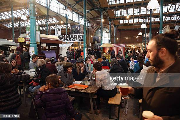 Visitors try out culinary delights from vendors on the first day of Street Food Thursday at the Markthalle Neun market hall in Kreuzberg district on...