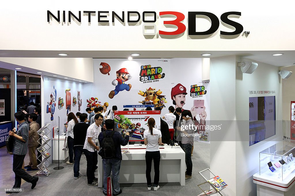 Visitors try out Nintendo Co. 3DS handheld game consoles in the company's booth at the World IT Show 2012 in Seoul, South Korea, on Tuesday, May 15, 2012. The show will be held through May 18. Photographer: SeongJoon Cho/Bloomberg via Getty Images