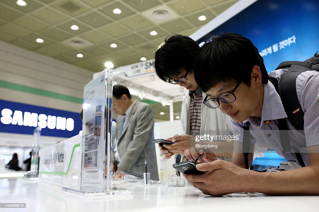 Visitors try out Samsung Electronics Co. Galaxy Note smartphones at the World IT Show 2012 in Seoul, South Korea, on Tuesday, May 15, 2012. The show will be held through May 18. Photographer: SeongJoon Cho/Bloomberg via Getty Images