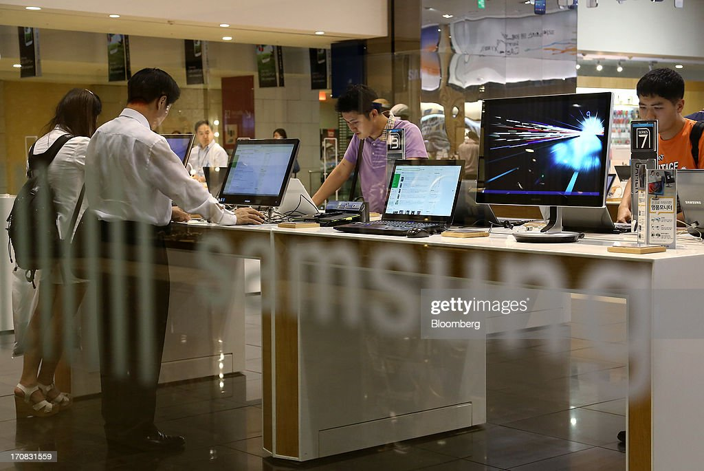 Visitors try out Samsung Electronics Co. laptop computers at the Samsung d'light store in Seoul, South Korea, on Tuesday, June 18, 2013. Facebook Inc. Chief Executive Officer Mark Zuckerberg, seeking to boost advertising sales from mobile devices, discussed potential partnerships with Samsung Electronics Co., according to the head of the South Korean companys handset division. Photographer: SeongJoon Cho/Bloomberg via Getty Images