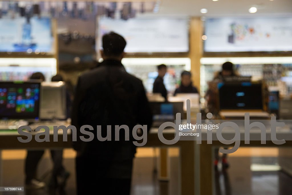 Visitors try out Samsung Electronics Co. laptop computers behind the company's logo at its flagship store in Seoul, South Korea, on Wednesday, Dec. 5, 2012. Samsung Electronics Co. promoted Lee Jae Yong to vice chairman, putting him a step closer to succeeding his father as leader of the world's biggest maker of televisions and mobile phones. Photographer: SeongJoon Cho/Bloomberg via Getty Images