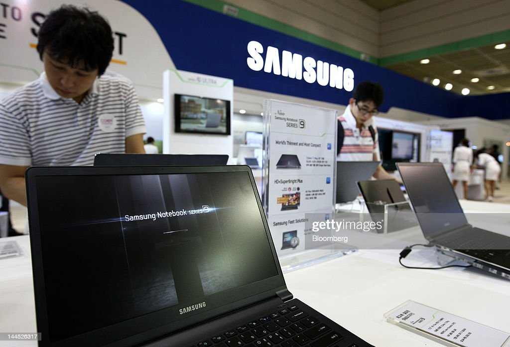 Visitors try out Samsung Electronics Co.'s laptop computers at the World IT Show 2012 in Seoul, South Korea, on Tuesday, May 15, 2012. The show will be held through May 18. Photographer: SeongJoon Cho/Bloomberg via Getty Images