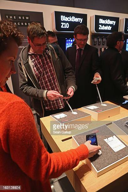 Visitors try out the Blackberry Z10 smartphone which is the Germany version of the Blackberry 10 at the Vodafone stand at the 2013 CeBIT technology...