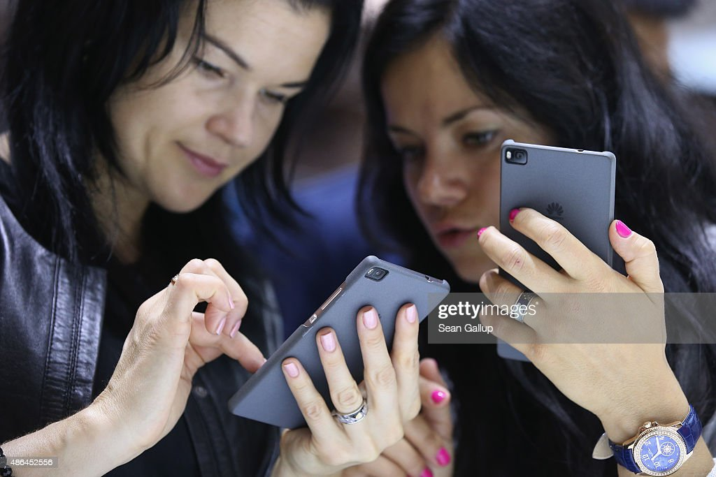 Visitors try out the Honor 7 smartphone at the Huawei stand at the 2015 IFA consumer electronics and appliances trade fair on September 4, 2015 in Berlin, Germany. The 2015 IFA will be open to the public from September 4-9.