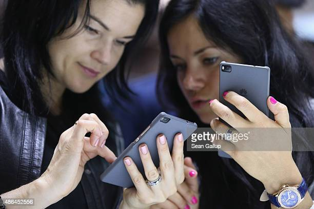 Visitors try out the Honor 7 smartphone at the Huawei stand at the 2015 IFA consumer electronics and appliances trade fair on September 4 2015 in...