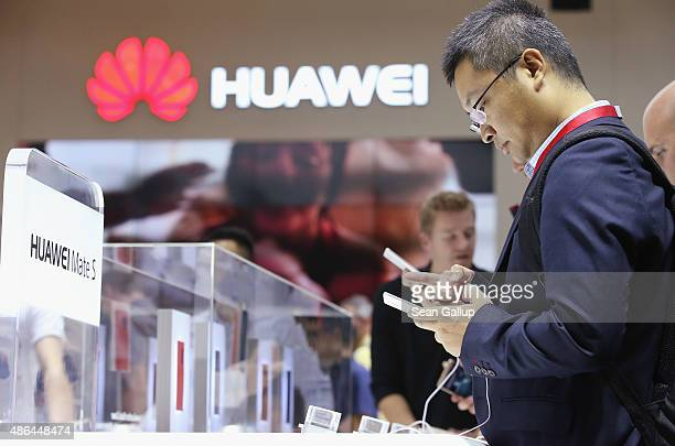 Visitors try out the Huawei Mate S smartphone at the Huawei stand at the 2015 IFA consumer electronics and appliances trade fair on September 4 2015...