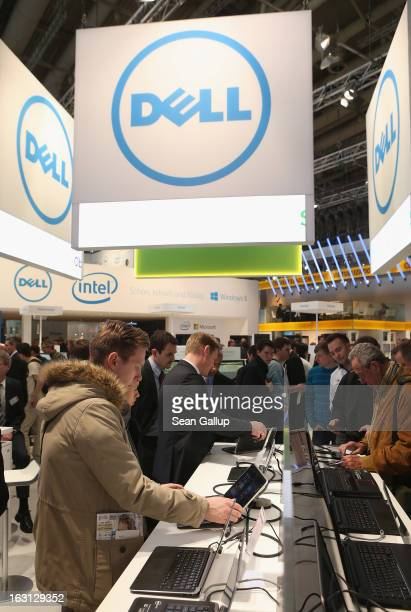 Visitors try out the latest laptop computers at the Dell stand at the 2013 CeBIT technology trade fair on March 5 2013 in Hanover Germany CeBIT will...