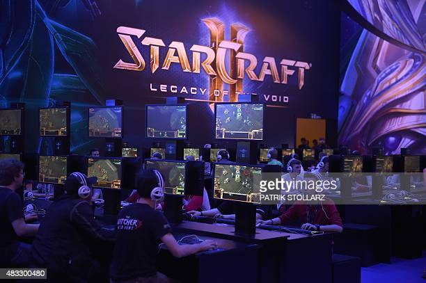 Visitors try out the latest version of Starcraft at the Gamescom fair in Cologne western Germany on August 7 2015 The trade fair for interactive...