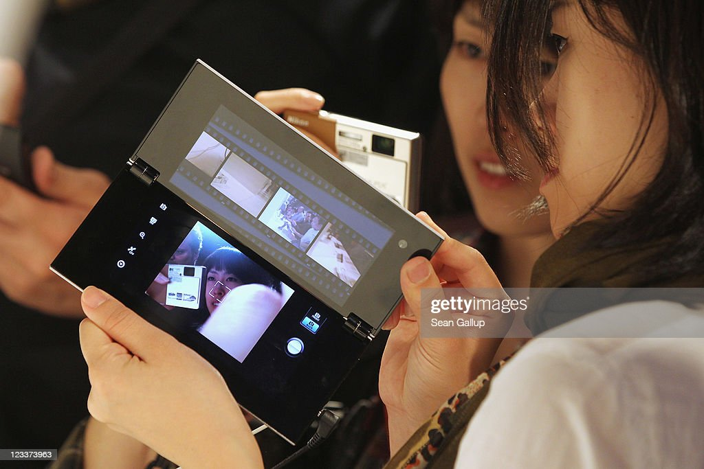 Visitors try out the new foldable Sony tablet PC at the Sony stand at the IFA 2011 consumer electonics and appliances trade fair on the first day of the fair's official opening on September 2, 2011 in Berlin, Germany. The IFA 2011 will be open to the public from September 2-7.