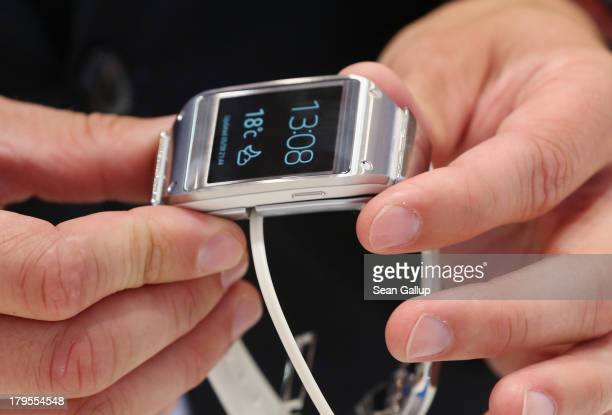 Visitors try out the new Galaxy Gear smartwatch at the Samsung stand at the IFA 2013 consumer electronics trade fair on September 5 2013 in Berlin...