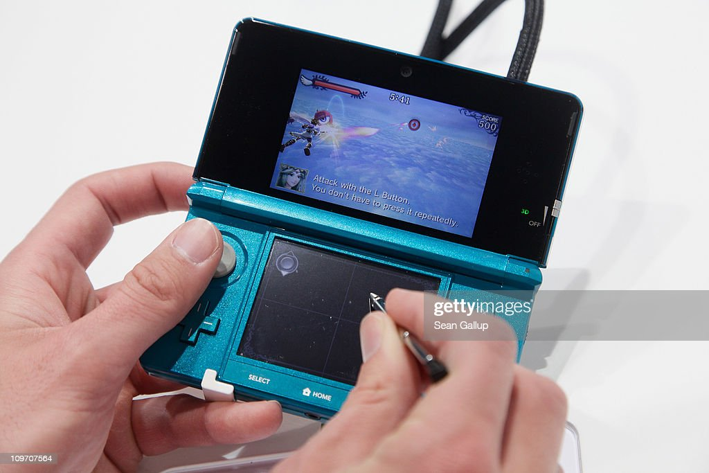 Visitors try out the new Nintendo 3DS handheld gaming device with a 3D display at the Nintendo DS stand at the CeBIT technology trade fair on March 2, 2011 in Hanover, Germany. CeBIT 2011 will be open to the public from March 1-5.