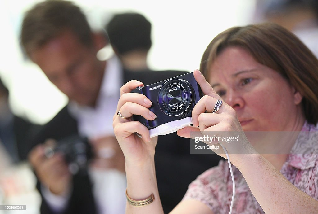 Visitors try out the new Samsung Galaxy Camera, which combines a smartphone and a digital camera with a zoom lens, during a press day at the Samsung stand at the IFA 2012 consumer electronics trade fair on August 30, 2012 in Berlin, Germany. IFA 2012 will be open to the public from August 31 through September 5.