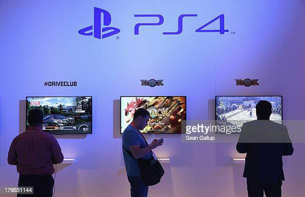 Visitors try out the PS4 gaming system at the Sony stand at the IFA 2013 consumer electronics trade fair on September 5 2013 in Berlin Germany The...