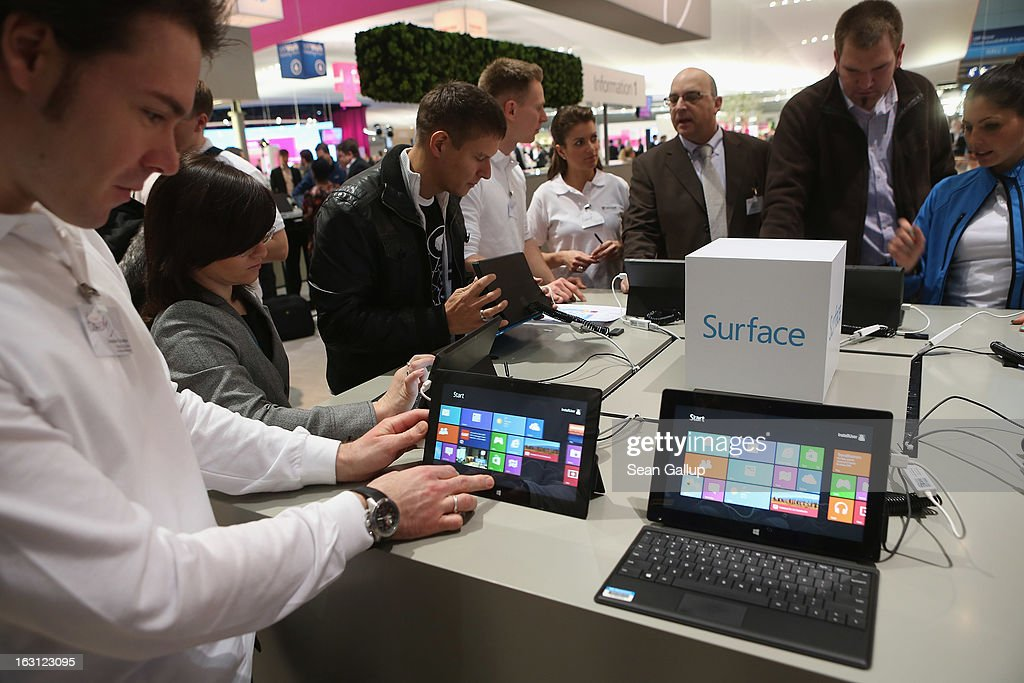 Visitors try out Windows 8 Surface tablet computers at the Microsoft stand at the 2013 CeBIT technology trade fair on March 5, 2013 in Hanover, Germany. CeBIT will be open March 5-9.