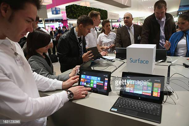 Visitors try out Windows 8 Surface tablet computers at the Microsoft stand at the 2013 CeBIT technology trade fair on March 5 2013 in Hanover Germany...