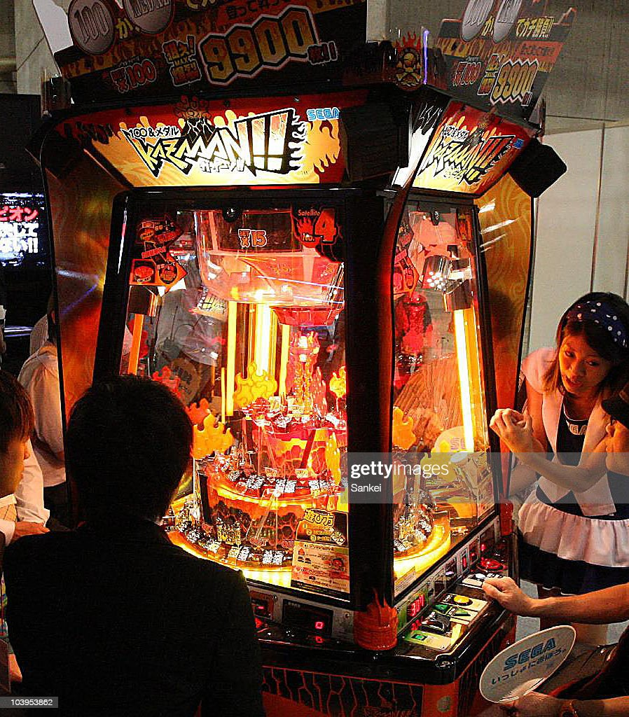 Visitors try Sega's '100&Medal Kazaan!!' during the 48th Amusement Machine Show at Makuhari Messe on September 9, 2010 in Chiba, Japan. The show, open until September 11, is for arcade video game machine industry, whose size of market has been shrinking year by year.