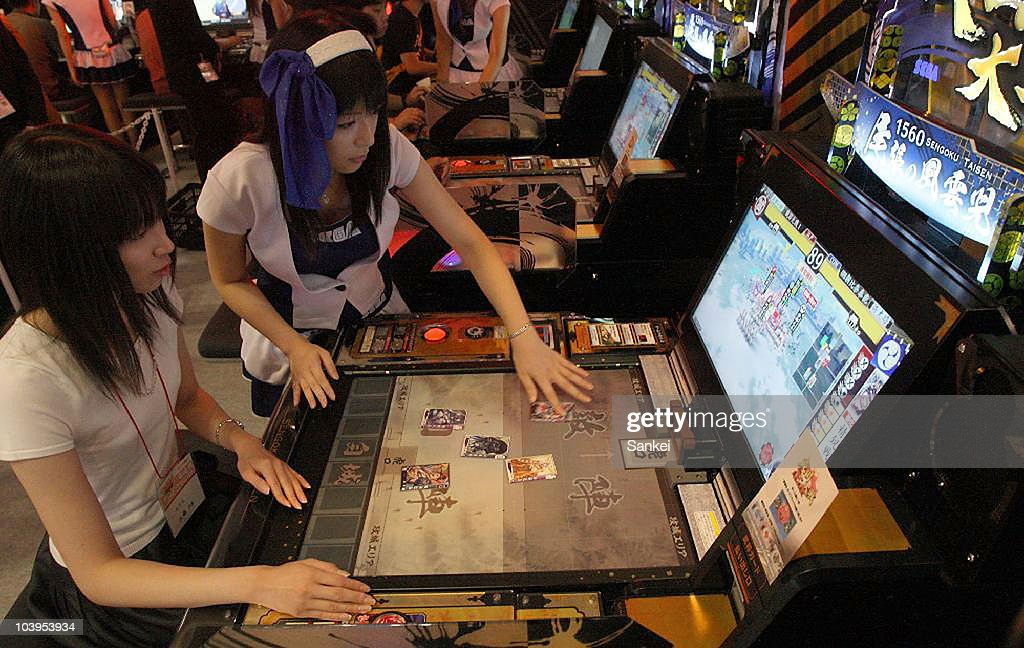 Visitors try Sega's 'Sengoku Taisen', online card game features histroic characters, during the 48th Amusement Machine Show at Makuhari Messe on September 9, 2010 in Chiba, Japan. The show, open until September 11, is for arcade video game machine industry, whose size of market has been shrinking year by year.