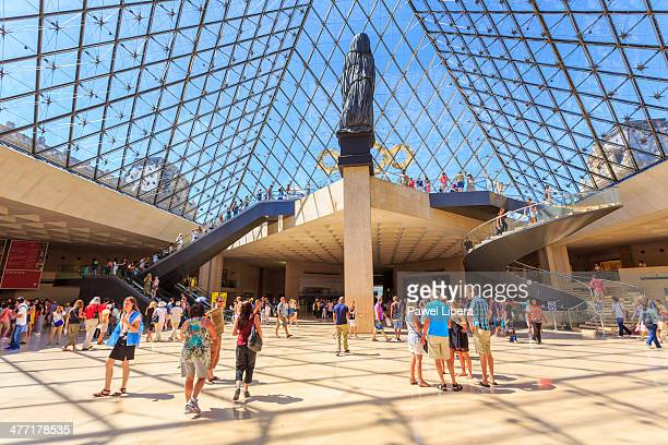 Visitors under the Pyramid inside Louvre Museum in Paris