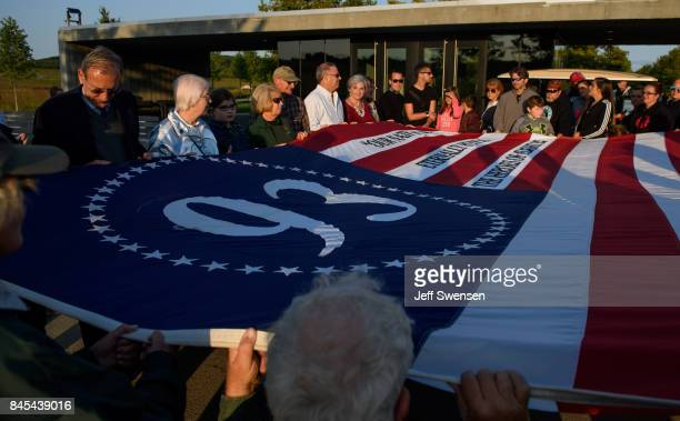Visitors unfurl a commemorative flag at the Flight 93 National Memorial on the 16th Anniversary ceremony of the September 11th terrorist attacks...