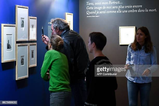 Visitors use a magnifying glass to view etchings by late Dutch painter and printmaker Rembrandt during an exhibition of a complete collection of 68...
