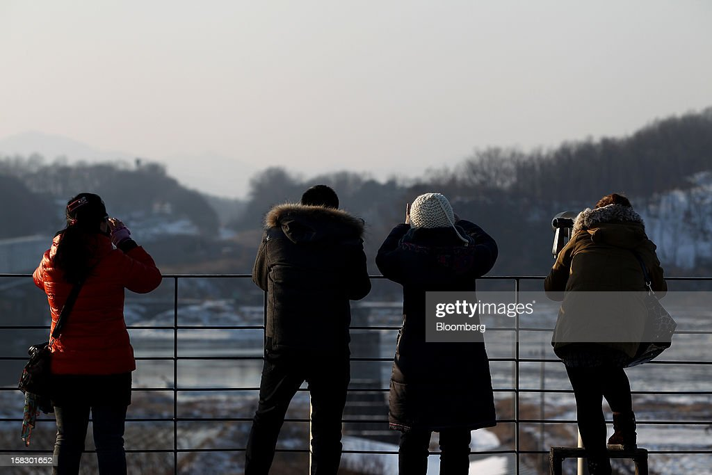 Visitors use binoculars as they look across to the north side of the border at the Imjingak pavilion near the demilitarized zone (DMZ) in Paju, South Korea, on Wednesday, Dec. 12, 2012. North Korea fired a rocket that placed a satellite into orbit, defying international sanctions and showcasing the nuclear-armed totalitarian regime's progress in ballistic missile technology. Photographer: SeongJoon Cho/Bloomberg via Getty Images