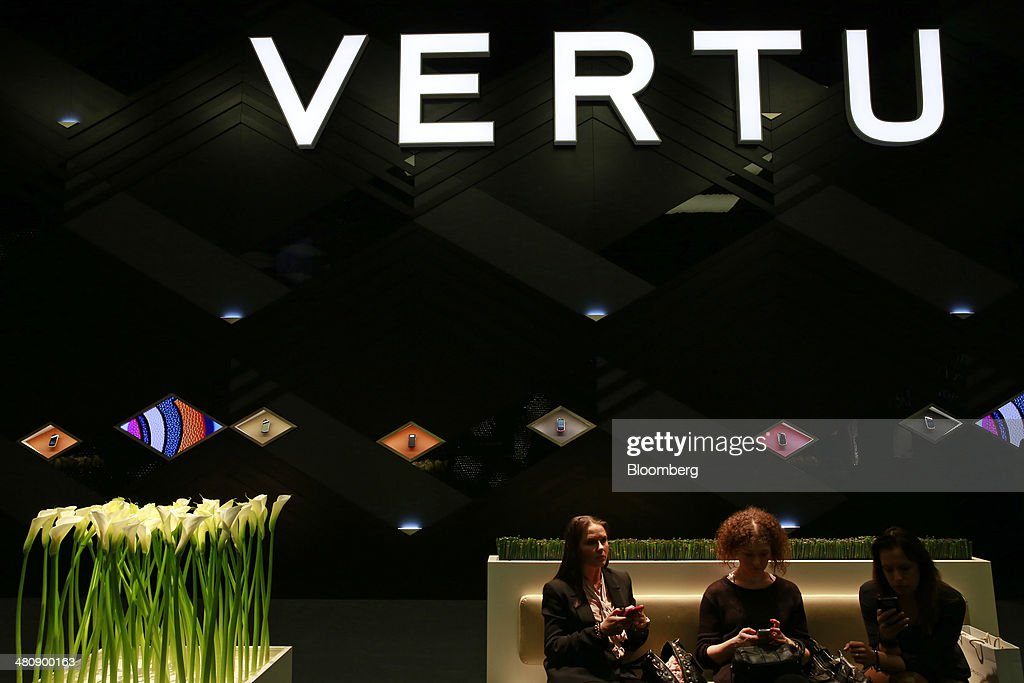 Visitors use mobile handsets as they sit outside the Vertu luxury mobile phone booth during the Baselworld luxury watch and jewelry fair in Basel, Switzerland, on Thursday, March 27, 2014. Over 1,400 companies from the watch, jewelry and gem industries will display their latest innovations and products to more than 120,000 visitors at this year's luxury show. Photographer: Gianluca Colla/Bloomberg via Getty Images