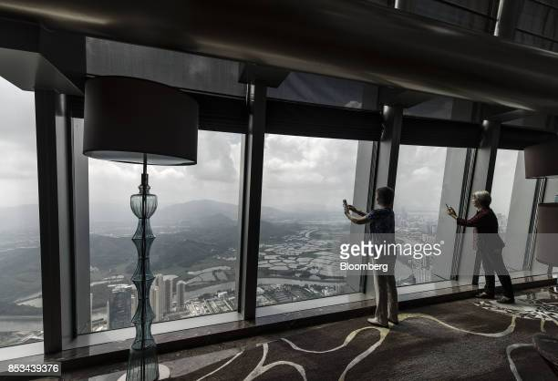 Visitors use their smartphones to take photographs from the observation deck of the KK100 tower in Shenzhen China on Wednesday Sept 20 2017 China is...