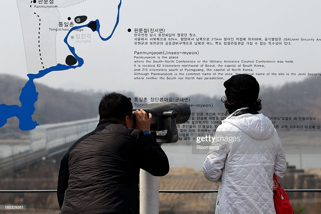 Visitors uses binoculars as they look across to the north side of the border at the Imjingak pavilion near the demilitarized zone (DMZ) in Paju, South Korea, on Wednesday, April 3, 2013. North Korea prevented South Korean workers from entering a jointly run industrial park today, adding to tensions after saying it will restart a mothballed nuclear plant and threatening to attack its southern neighbor. Photographer: SeongJoon Cho/Bloomberg via Getty Images