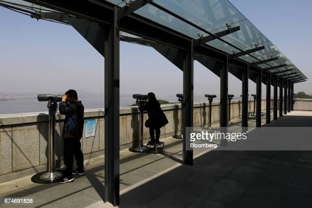 Visitors using binoculars look at the North Korean village of GaepungGun at the Odusan Unification Observatory near the Demilitarized Zone in Paju...