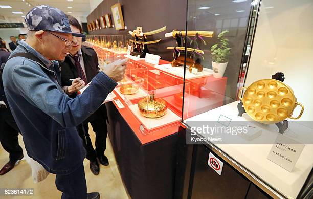 Visitors view a 432 million yen pure gold 'takoyaki' dumpling maker at Takashimaya Co department store in the western Japan city of Osaka on Nov 17...
