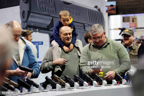 Visitors view a gun display at a National Rifle Association outdoor sports trade show on February 10 2017 in Harrisburg Pennsylvania / AFP / DOMINICK...