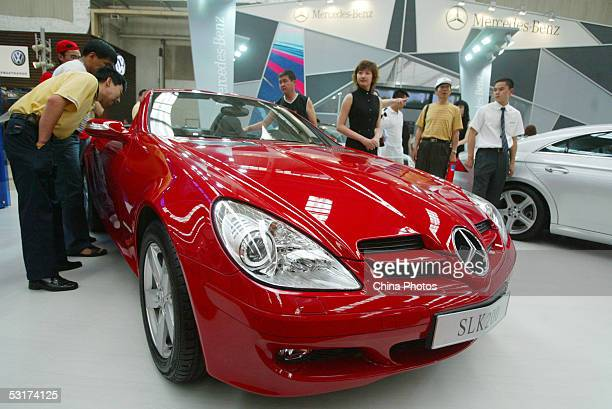 Visitors view a new Mercedes SLK200 sports car at the 2005 China Shenyang International Auto Industry Exposition June 30 2005 in Shenyang Liaoning...