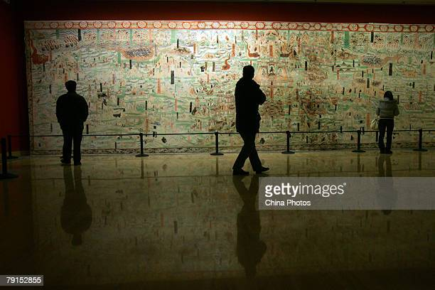 Visitors view a replica of a 13meterlong fresco from the Mogao Cave during the Dunhuang Art Exhibition at the National Art Museum of China on January...