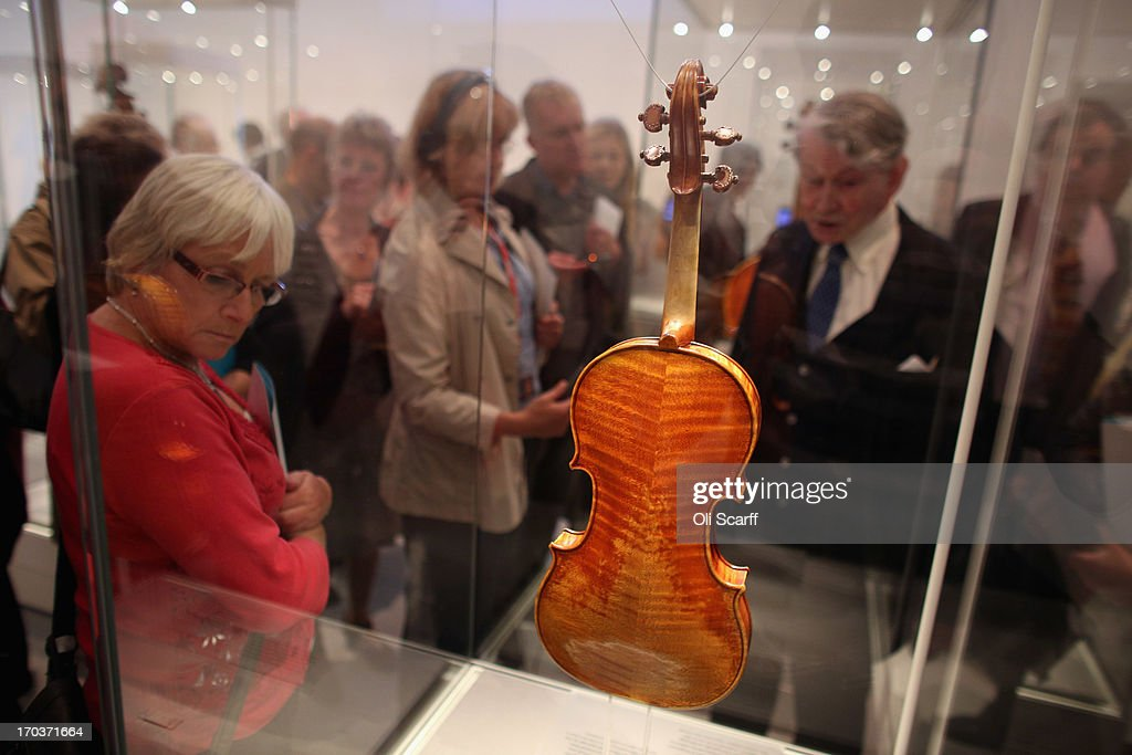 Visitors view a violin made by Antonio Stradivari on show at the exhibition 'Stradivarius' at the Ashmolean museum on June 12, 2013 in Oxford, England. The exhibition, which is the first major show of Stradivarius instruments in the UK, brings together 21 violins and cellos and runs until August 11, 2013.