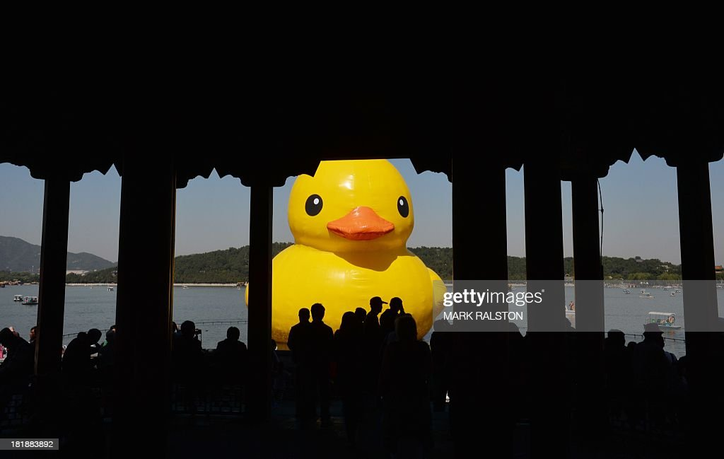 Visitors view an 18-metre tall inflatable duck after its move to Lake Kunming at the historic Summer Palace in Beijing on September 26, 2013. The duck designed by Dutch artist Florentijn Hofman is to be displayed at Beijing's Garden Expo Park and the Summer Palace, from September to October as part of a world tour of 13 cities across 10 countries. AFP PHOTO / Mark RALSTON