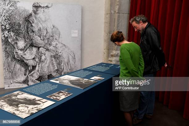 Visitors view an etching's enlargement 'Jacob caressing Benjamin' circa 1637 during an exhibition of a complete collection of 68 original etchings by...