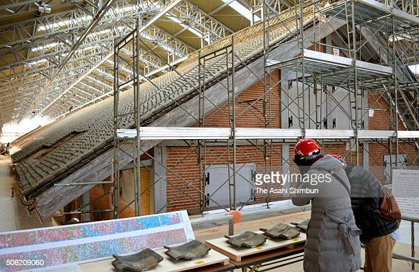 Visitors view the repair and preservation work being conducted on the roof of the West Cocoon Warehouse of the Tomioka Silk Mill on January 22 2016...