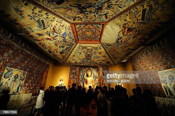 Visitors visit a replica parts of the Mogao Cave during the Dunhuang Art Exhibition in Beijing on February 20 2008 The exhibition displays...