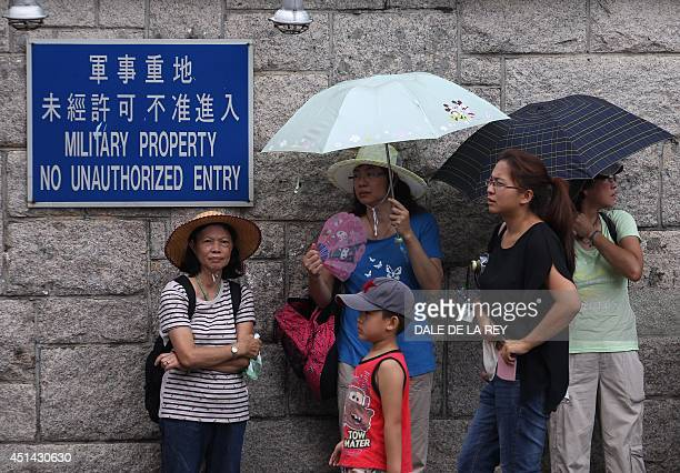 Visitors wait in a queue before an open day at the Chinese People's Liberation Army Shek Kong Barracks in Hong Kong on June 29 2014 The Hong Kong...