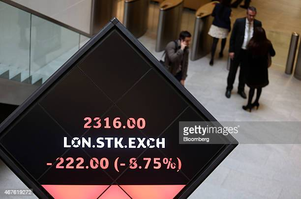 Visitors wait near an illuminated rotating cube displaying share price information for the London Stock Exchange as it stands in the atrium of the...