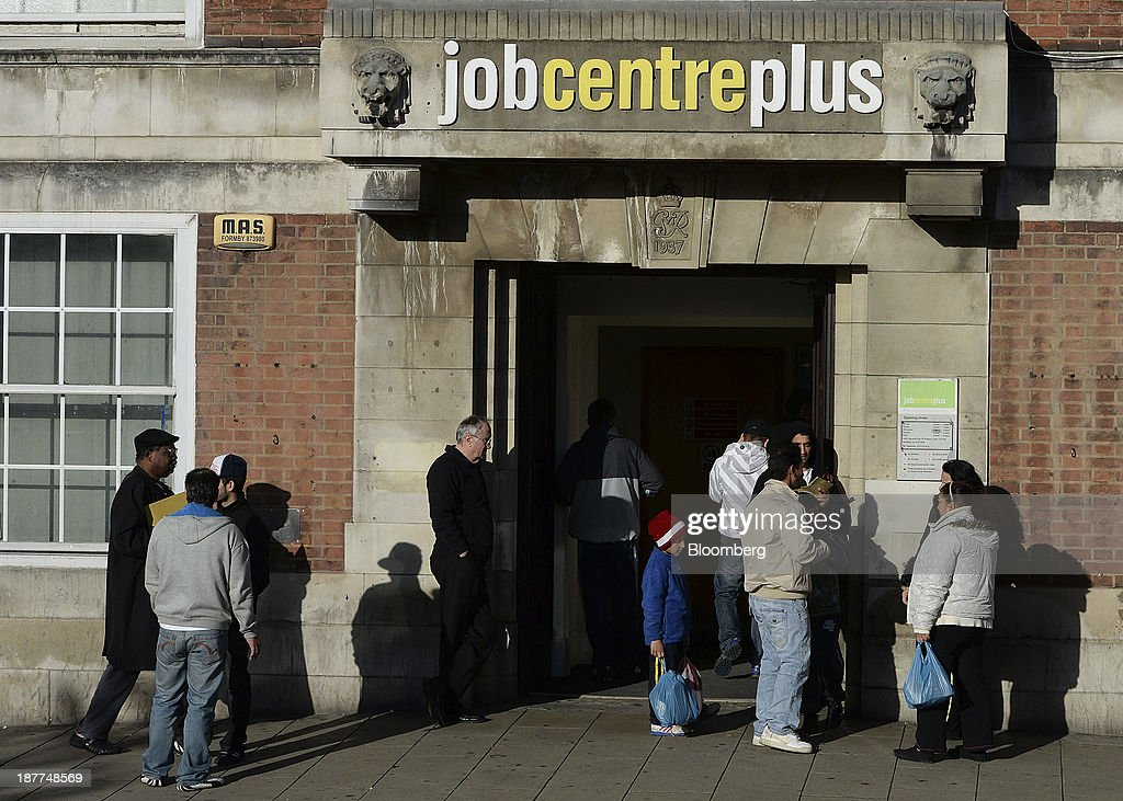 Visitors wait to enter a job centre in Leeds, U.K., on Tuesday, Nov. 12, 2013. Under Bank of England Governor Mark Carney's forward-guidance policy, the central bank has pledged to not to withdraw stimulus at least until unemployment falls to 7 percent. Photographer: Nigel Roddis/Bloomberg via Getty Images