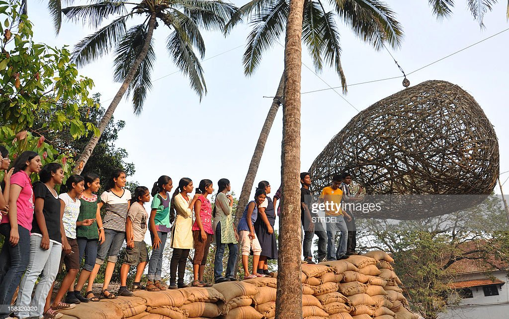 Visitors wait to see the installation work 'Erase' by Bangalore based artist Srinivasa prassad at the Kochi-Muziris Biennale 2012 exhibition in Kochi on December 13, 2012. The Kochi-Muziris Biennale will span over 3 months from December 12, 2012 to March 13, 2013 and will feature the works of over 80 major artists from more than 24 countries. This is the first-ever biennale to be held in India. AFP Photo/ STR