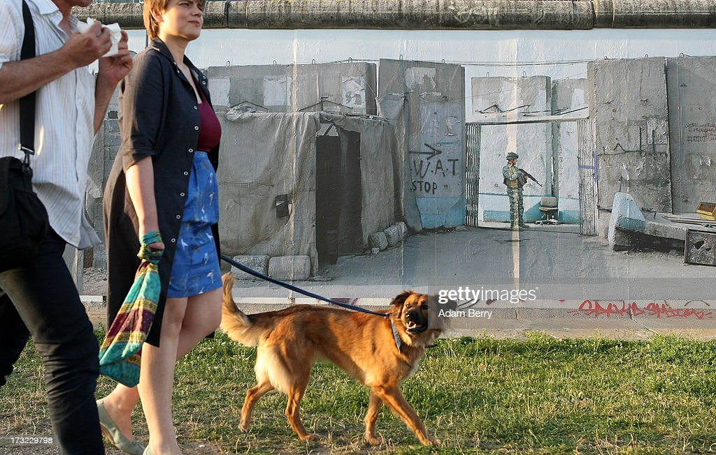 Visitors walk a dog past a photo of the Baghdad Wall in Iraq in the 'Wall on Wall' exhibition at the East Side Gallery section of the former Berlin Wall on July 10, 2013 in Berlin, Germany. A series of photos shot since 2006 by photographer Kai Wiedenhoefer hanging on the Western, river Spree side of the Wall features large pictures of separation barriers in Baghdad, Korea, Cyprus, Mexico, Morocco, Israel, Belfast, and in the former East Germany itself. The opposite side of the stretch of the original Wall is known as East Side Gallery, a memorial to peace and freedom covered in murals questioning the legacy of the original Wall, and the subject of several demonstrations earlier in March this year when sections of it were threatened with removal to make way for a construction site for luxury apartment buildings, discussion of which is still ongoing with a decision expected to be reached in early August.