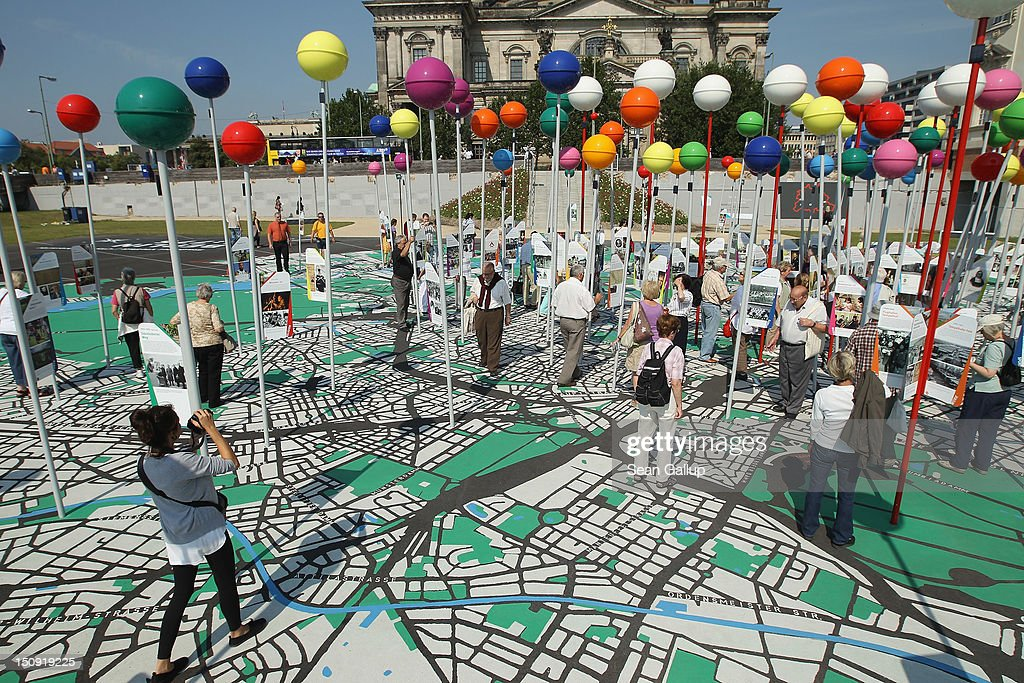 Visitors walk across a giant map of Berlin in 1:775th scale complete with giant, coloured pins marking sites of historical significance on August 29, 2012 in Berlin, Germany. The map is part of ongoing exhibitions and events ahead of Berlin's 775th anniversary, which the city will mark with a celebration scheduled for the end of October.