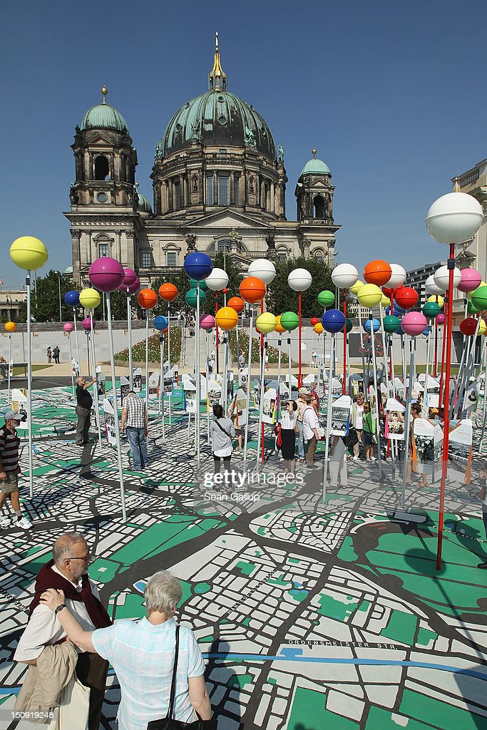 Visitors walk across a giant map of Berlin in 1:775th scale complete with giant, coloured pins marking sites of historical significance as the Dom cathedral is visible behind on August 29, 2012 in Berlin, Germany. The map is part of ongoing exhibitions and events ahead of Berlin's 775th anniversary, which the city will mark with a celebration scheduled for the end of October.