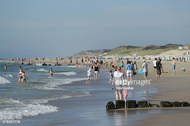 Visitors walk along a beach on Sylt Island on July 19 2016 near Wenningstedt Germany Sylt Island with its long stretches of sand beaches and its...