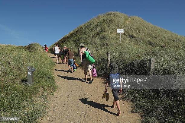 Visitors walk along a path among protected sand dunes after a day at the beach on Sylt Island on July 19 2016 near Wenningstedt Germany Sylt Island...