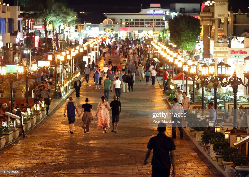 Visitors walk along a road containing bars and shops at night in Naama Bay on May 30, 2011 in Sharm El Sheikh, Egypt. Protests in January and February brought an end to 30 years of autocratic rule by President Hosni Mubarak who will now face trial. Food prices have doubled and youth unemployment stands at 30%. Tourism has yet to return to pre-uprising levels.